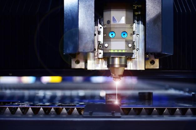 Industriële lasersnijmachine tijdens het snijden van het plaatwerk met het vonkende licht. Premium Foto