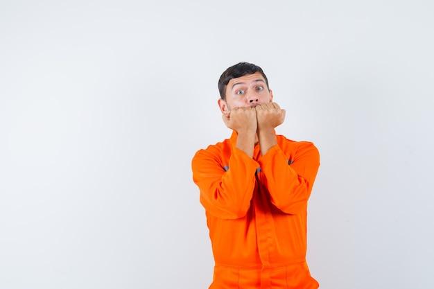 Industriële man emotioneel bijten vuisten in uniform en bang op zoek. vooraanzicht. Gratis Foto