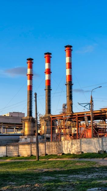 Industriële ondernemingen met pijpen tegen de blauwe lucht. Premium Foto
