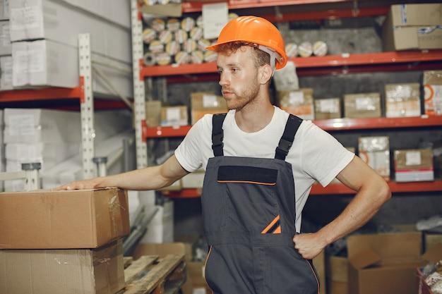 Industriële werknemer binnenshuis in fabriek. jonge technicus met oranje bouwvakker. Gratis Foto