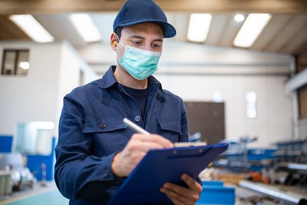Industriële werknemer die op een document in een fabriek schrijft Premium Foto
