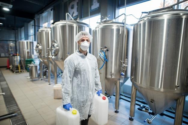 Industriële werknemer technoloog in wit beschermend pak met haarnetje en masker met plastic blikjes met chemicaliën in de productielijn van de voedselfabriek Gratis Foto