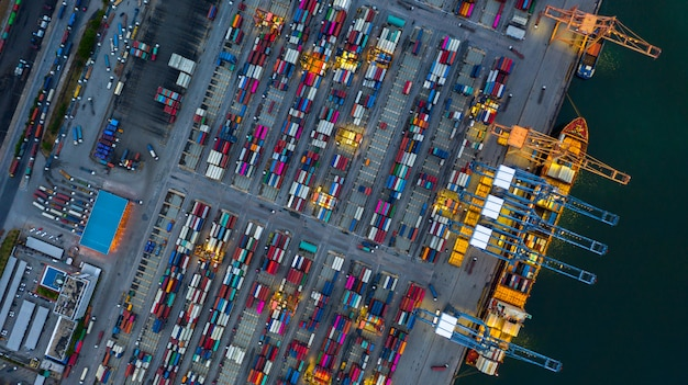 Industriële zeehaven werken 's nachts met containerschip werken' s nachts, luchtfoto containerschip laden en lossen 's nachts. Premium Foto