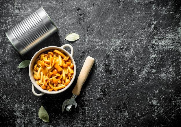 Ingeblikte champignons in een kom met een blikje en een blikopener op donkere houten tafel Premium Foto