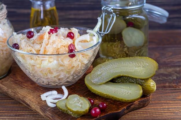 Ingelegde komkommers in een glazen pot op een houten bord en zuurkool met veenbessen. gefermenteerd voedsel. kopieer ruimte. Premium Foto