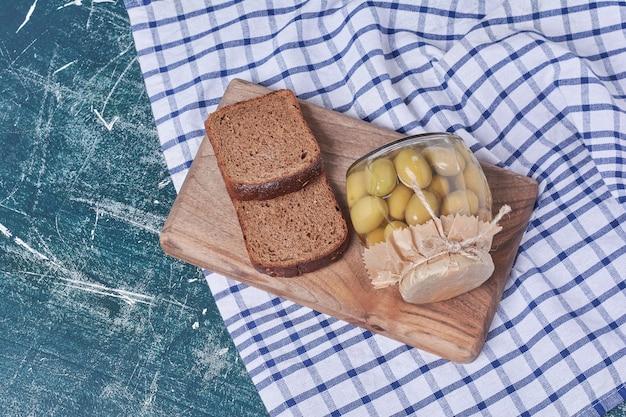 Ingelegde olijven in glazen pot met zwarte sneetjes brood op blauw. Gratis Foto