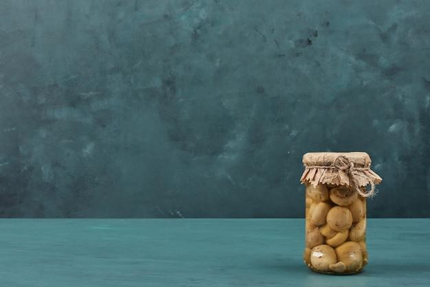 Ingemaakte champignons in een glazen pot op blauwe tafel. Gratis Foto