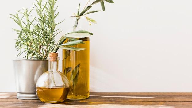 Ingemaakte rozemarijn met olijfolieflessen op houten lijst Gratis Foto