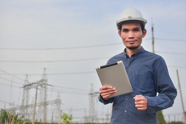 Ingenieur bedrijf tablet buiten hoogspanning systeemachtergrond Premium Foto