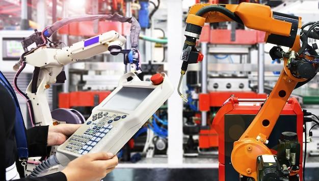 Ingenieur controleert en stuurt moderne hoogwaardige lasrobots voor automatisering bij industriële toepassingen Premium Foto