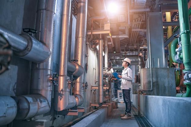 Ingenieur controleert statuswerk in fabriek, stalen pijpleidingen en kleppen in industriële zone, onderhoudsapparatuur voor ingenieurs in energiecentrale. Premium Foto