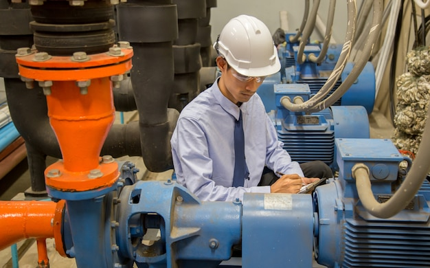 Ingenieur controleren condensor waterpomp en manometer, koelmachine waterpomp met manometer. Premium Foto