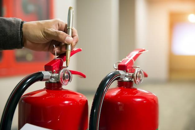 Ingenieur die brandblusapparaat controleert Premium Foto