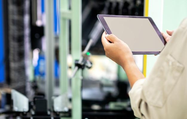 Ingenieur die digitale tablet gebruiken voor het testen van de werking van de machine in de fabrieksfabriek Premium Foto