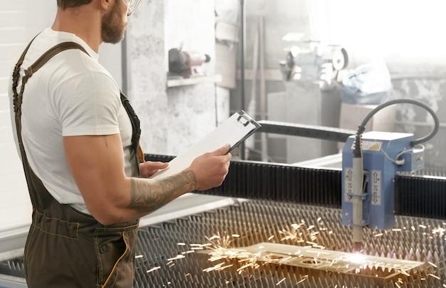 Ingenieur die plasma lasersnijdend metaal controleert. Gratis Foto