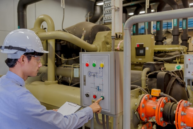 Ingenieur die werkende industriële koelmachines, warm waterpomp en pijplijn controleert voor maakt op hoge temperatuurstoestand in hvac-systemen. Premium Foto