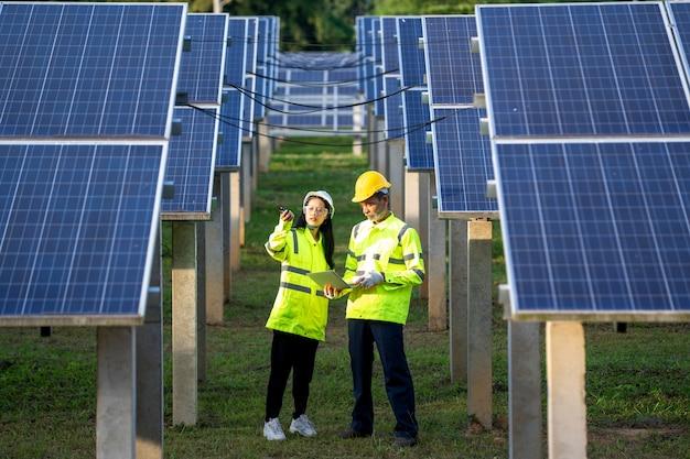Ingenieur en technicus die apparatuur in zonnepanelen controleert. Premium Foto