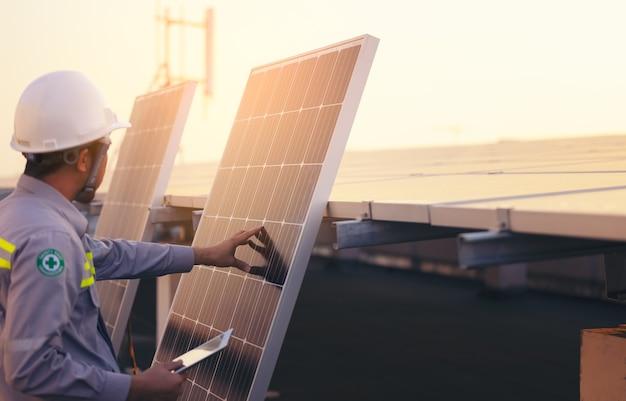 Ingenieur fotovoltaïsche zonnepanelen stationcontroles met tabletcomputer. energie technologie concept Premium Foto