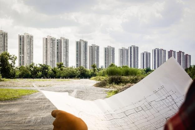 Ingenieur kijken en plannen van architect met blauwdruk bouw website projecten bouwen Premium Foto