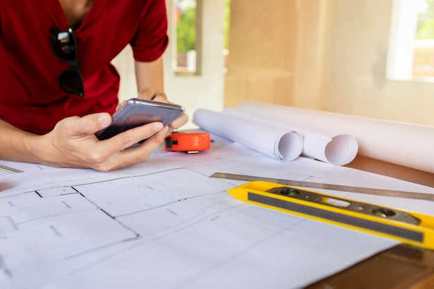 Ingenieur of architect die celtelefoon in bouwconstructieplaats met behulp van. Premium Foto
