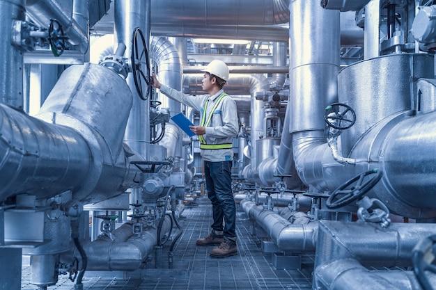 Ingenieur werkende terugslagklep en pijp in de fabriek, industriële zone stalen pijpleidingen en kleppen, ingenieur onderhoudsapparatuur bij elektriciteitscentrale Premium Foto