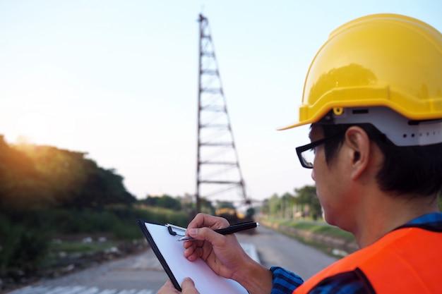 Ingenieurs houden het klembord vast, controleer de materiaallijst in het constructiegebied Premium Foto