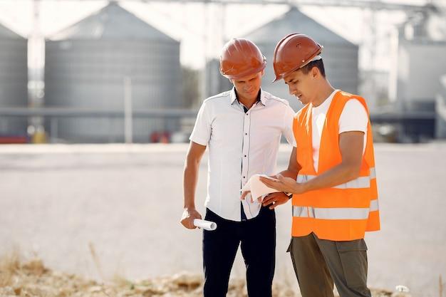 Ingenieurs in helmen staan door de fabriek Gratis Foto