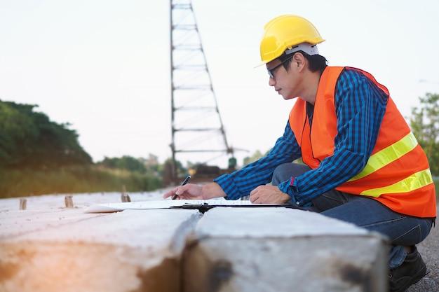 Ingenieurs lezen de blauwdruk die op palen in het bouwgebied wordt geplaatst Premium Foto