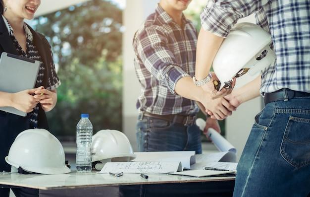 Ingenieurs schudden elkaar de hand samen met het secretaresse meisje aan de zijkant. Premium Foto