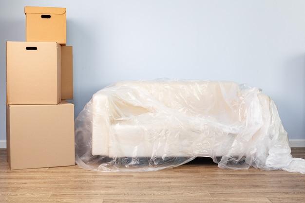 Ingepakte huishoudelijke spullen in dozen en een verpakte bank om te verplaatsen Premium Foto