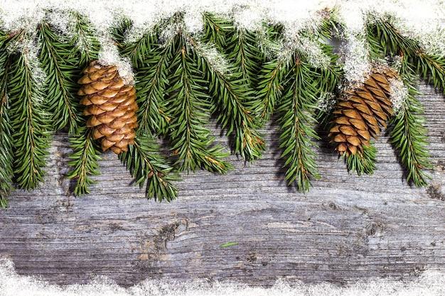 Ingerichte pijnboomtakken met kegels op houten tafel vrije ruimte. kerst versiering Premium Foto