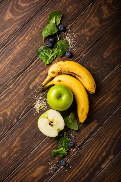 Ingrediënten fot gezond ontbijt detox groene smoothie kom van banaan, appels en spinazie op houten oppervlak. uitzicht van boven Premium Foto