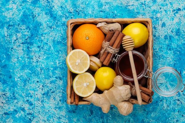 Ingrediënten: verse gember, citroen, kaneelstokjes, honing, gedroogde kruidnagel voor het maken van immuniteit stimuleren van gezonde vitaminedrank Gratis Foto