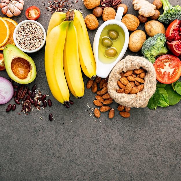 Ingrediënten voor de gezonde voedselselectie. het concept gezonde voedselopstelling op donkere concrete achtergrondexemplaarruimte. Premium Foto