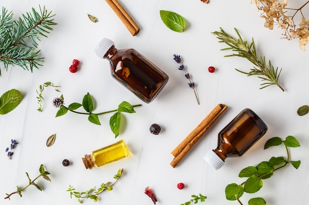 Ingrediënten voor etherische olie. verschillende kruiden en flessen etherische olie, witte achtergrond, flatlay. Premium Foto