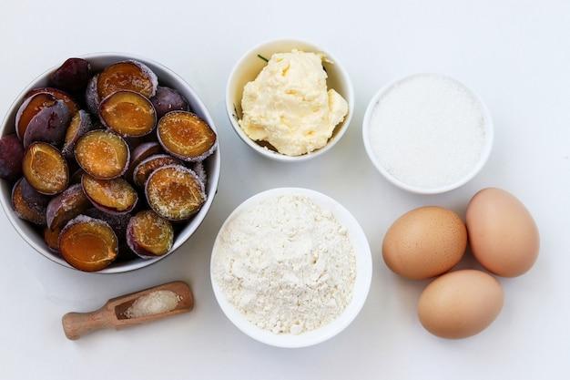 Ingrediënten voor het bakken van de pruimcake op een wit Premium Foto