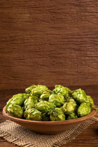 Ingrediënten voor het brouwen van bier hopbellen in houten kom en tarweoren op houten achtergrond. bierbrouwerij concept. Premium Foto