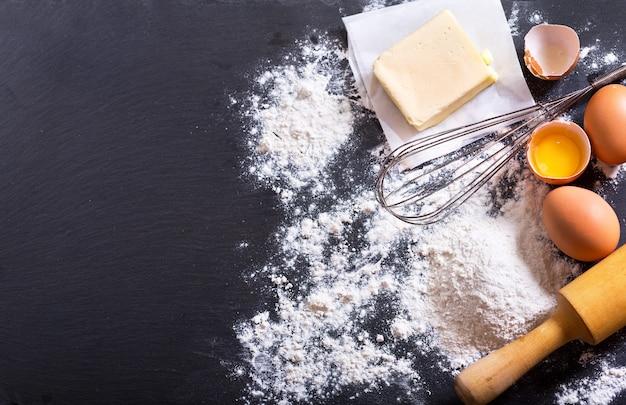 Ingrediënten voor het koken: bloem, boter, eieren op donker Premium Foto