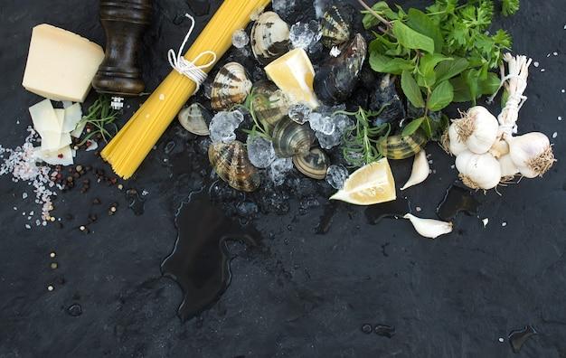 Ingrediënten voor het koken spaghetti vongole. tweekleppige schelpdieren op afgebroken ijs, rauwe pasta, parmezaanse kaas, knoflook, peterselie en citroen over stenen leisteen, bovenaanzicht Premium Foto