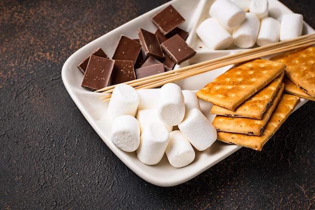 Ingrediënten voor het roosteren van marshmallows en het koken van s'mores Premium Foto