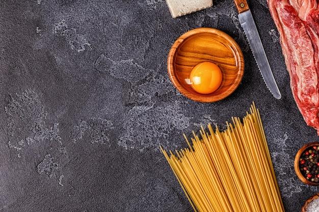 Ingrediënten voor pasta carbonara op een cementtafel Premium Foto
