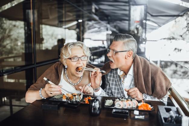 Inhoud man en vrouw zitten op zomerterras sushi eten en samen tijd doorbrengen Premium Foto