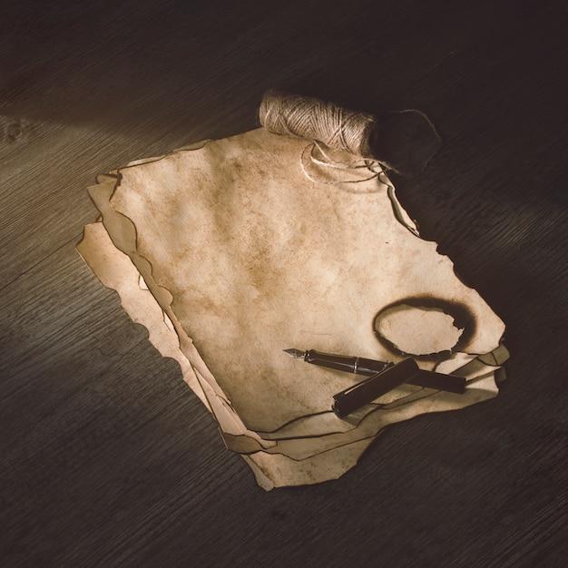 Inktpen en linnen draad op verbrand papier Gratis Foto