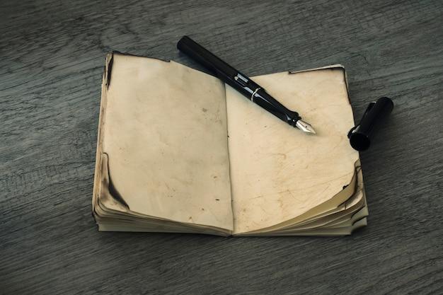 Inktpen op geopend oud notitieboekje Gratis Foto