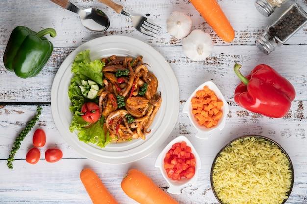 Inktvis gebakken met currypasta in witte plaat, met groenten en bijgerechten op een witte houten vloer. Gratis Foto