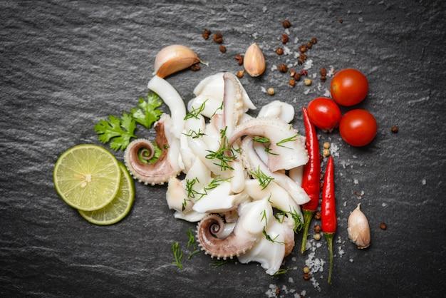 Inktvis salade met citroen kruiden en specerijen op donkere achtergrond bovenaanzicht tentakels octopus gekookt voorgerecht eten warm en pittige chili saus zeevruchten gekookt geserveerd op zwarte plaat in het restaurant Premium Foto