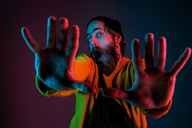 Inlijsten, selfie. kaukasisch man's portret op de achtergrond van de gradiëntstudio in neonlicht. mooi mannelijk model met hipsterstijl. concept van menselijke emoties, gezichtsuitdrukking, verkoop, advertentie. Gratis Foto