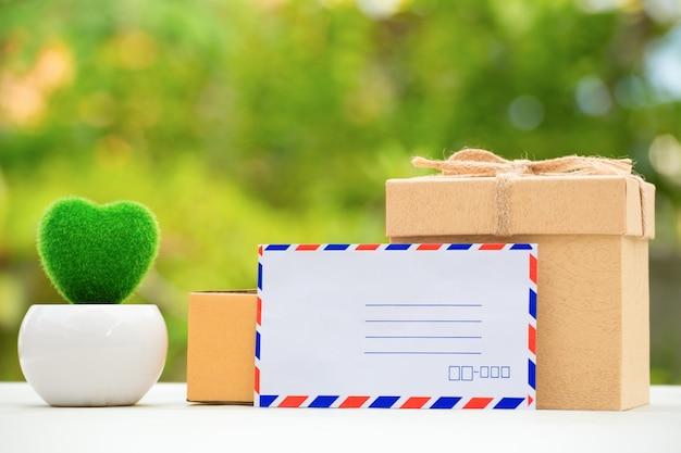 Inpakkende bruine pakjesdoos op mooie natuurlijke groene achtergrond. Premium Foto