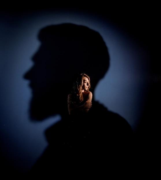 Inschrijving kaukasisch blondemeisje met gesloten ogen bevindt zich in de man hoofdschaduw op de blauwe muur Gratis Foto