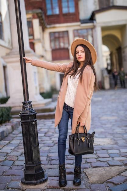 Inschrijving lachende dame loopt op straat en poseren in casual moderne jas en hoed Gratis Foto
